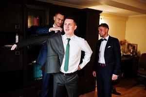 Groomsmen helping groom to dress up
