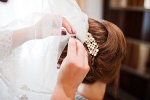 Bridesmaid pinning veil to bride's h