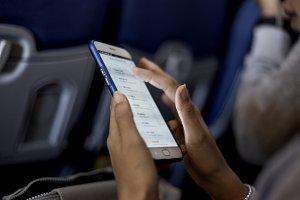 woman using smartphone airplane