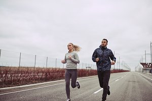 Diverse young couple running along a