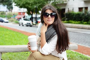 Woman holding paper coffee cup in th