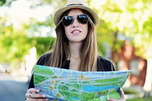 Young tourist woman looking at a map