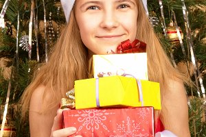 Teen girl in Christmas cap holding