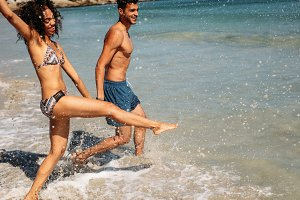 Couple playing in water on the beach
