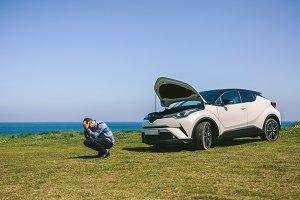 Young man desperate, car broken down