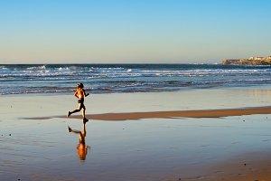 Woman running ocean beach sunset