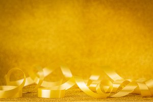 Curly yellow ribbon on golden backgr