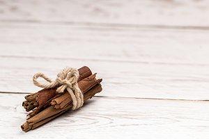 Cinnamon sticks tied on wooden table
