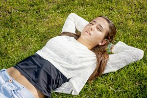 Beautiful teenager lying on the gras
