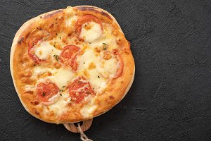 Pizza Margherita on black stone