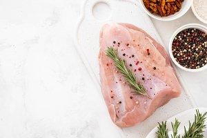 Raw turkey breast fillets on wooden