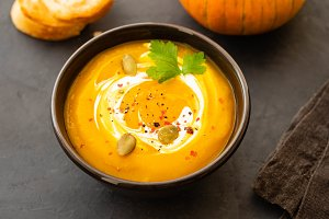 Pumpkin soup in a bowl with fresh