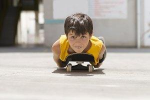 A Funny boy lying on a skateboard