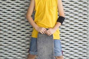 A teenage boy carrying skateboard an