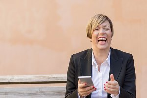 Business woman smiling with a mobile