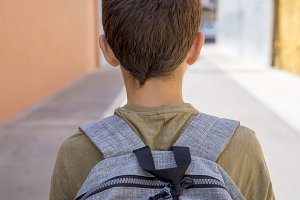 Cheerful child carrying his backpack
