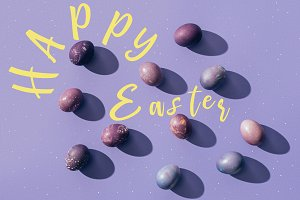 painted eggs on purple background wi
