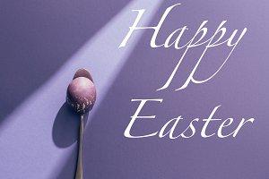 painted egg in spoon on purple backg