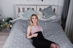 Blonde girl in dress posed on bed ne