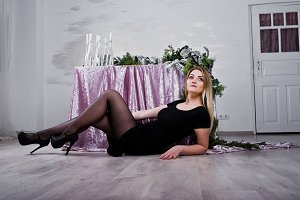 Blonde girl in black dress posed nea