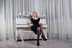 Blonde girl in black dress posed nea