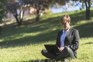 A businesswoman Sitting In Field Usi