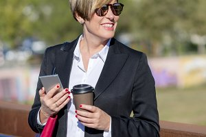 Businesswoman with smartphone standi