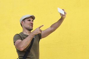 Funny man taking selfie and showing