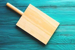 Wooden cutting board on green