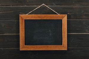 Empty blackboard hanging on wooden w