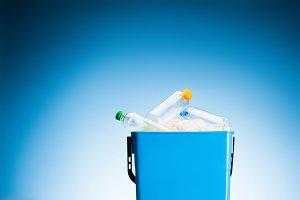 plastic bottles in trash bin on blue