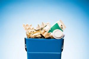 various paper trash in trash bin on
