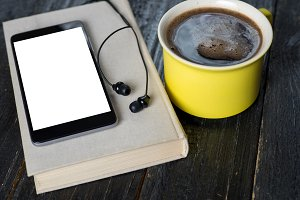 Coffee mug, headphones and book on w