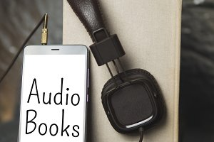 headphones and book on wooden dark b