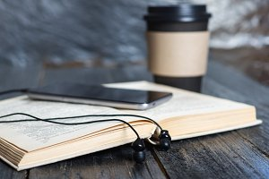 Coffee mug, headphones and a book. T