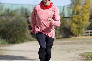 Senior man wearing glasses jogging a