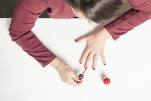 Woman painting her nails in red. Abo