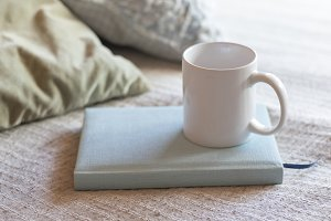 A tea cup on book over bed
