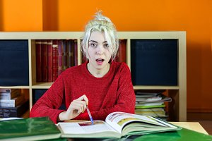Surprised young woman while studying
