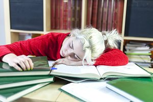 Tired blonde student woman sleeping