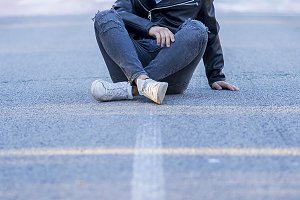 Stylish teenager sitting on the road