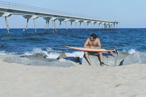 Surfer waxing the board at the beach