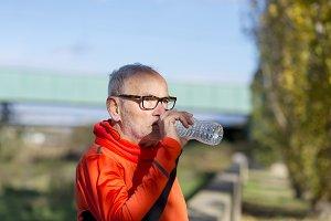 Handsome senior jogging man drinking