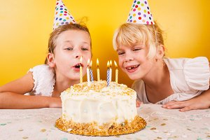 Girls blowing out candles on cake