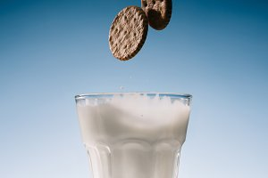 Two biscuits falling into glass of m