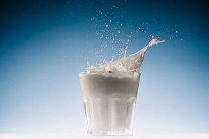 Glass with milk and splashes isolate