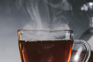 Steaming black tea in glass cup on t