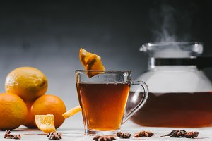 Black tea in cup with lemons and sta