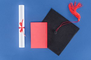 Graduation cap with diploma and book
