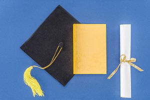 Graduation hat with diploma and book